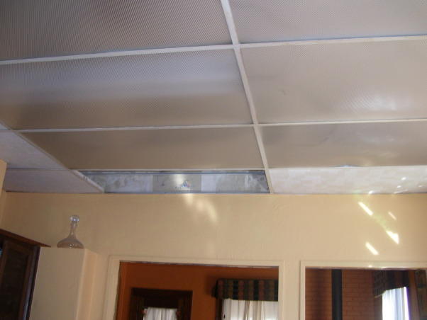 drop ceilings be gone remodel, we remodeled our kitchen on a very limited budget.  We raised up the torn up drop ceilings.  We tore out the plaster ceilings ourtselves (talk about messy).  We installed new tile countertops (never did tiling before), and we knocked out part of a wall/window to open up the kitchen to the dining area.  , ugly drop ceilings took 2 feet off of these high ceilings, making the kitchen look much more cramped. , Kitchens Design