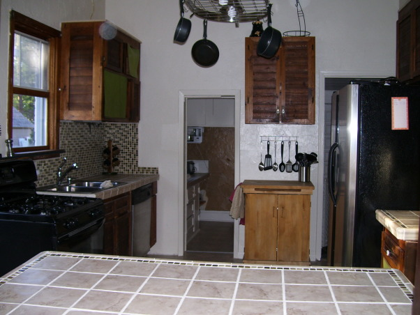 drop ceilings be gone remodel, we remodeled our kitchen on a very limited budget.  We raised up the torn up drop ceilings.  We tore out the plaster ceilings ourtselves (talk about messy).  We installed new tile countertops (never did tiling before), and we knocked out part of a wall/window to open up the kitchen to the dining area.  , the kitchen looks less pieced together, with the tile counters and high ceilings., Kitchens Design