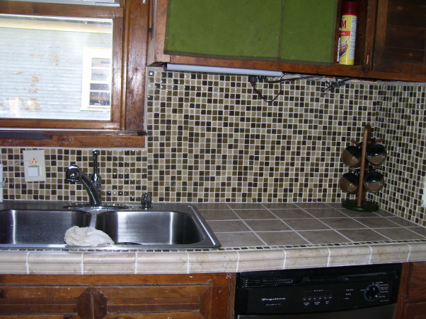 drop ceilings be gone remodel, we remodeled our kitchen on a very limited budget.  We raised up the torn up drop ceilings.  We tore out the plaster ceilings ourtselves (talk about messy).  We installed new tile countertops (never did tiling before), and we knocked out part of a wall/window to open up the kitchen to the dining area.  , we added a backsplash, which adds a lot more character., Kitchens Design