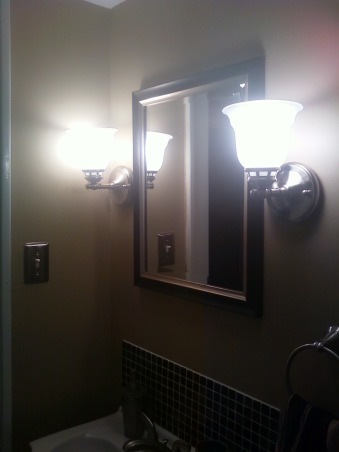 RENOVATED BATHROOM!, LOOK AT THIS WONDERFUL RENOVATED HALF BATH!, OK here is a picture of the two light fixtures that we purchased from Lowe's.  The display at Lowe's shows you to point these lights down, but we switched them around to point up!  That was a good idea, because it gives more light in the bathroom.  The mirror, I purchased at local store call Ollie's.  It's like a bargain store.  Got it for $12.99!  Great deal right!  You can also see in the picture that the outlet covers are also brushed nickel.  The lights are brushed nickel as well., Bathrooms Design
