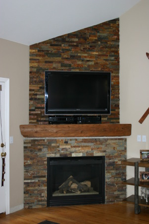 Fireplace Update, We needed a new space to fit in with the room and accommodate the flat TV.  We took old tile down, framed out the old Media hole, and found a nice reclaimed piece of wood to compliment the stacked stone tile., Finished stone wall with the TV wall mounted   , Other Spaces Design