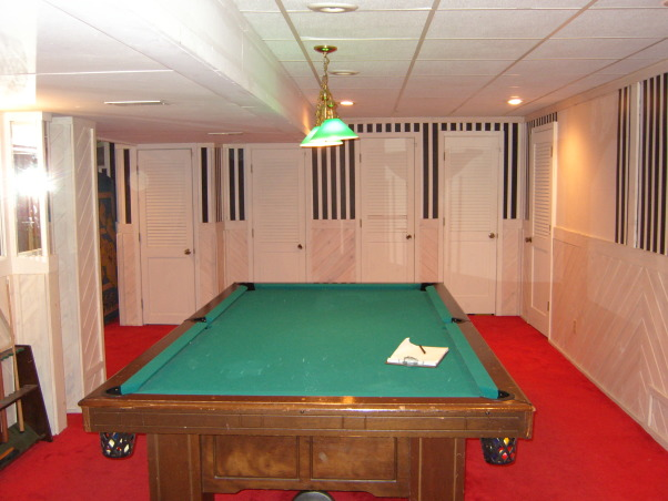 "Basement Remodel, Once an ugly basement with bright red carpet and drop ceiling becomes a cool space for kids, theater, poker, exercise, and more. Note the stained concrete floor and louvered <a href=""http://www.shutterland.net"">exterior shutters</a> are used as doors., Basement Before: doors, doors, doors, prison-striped wallpaper, ugly drop ceiling   , Basements Design"