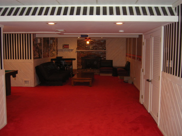 "Basement Remodel, Once an ugly basement with bright red carpet and drop ceiling becomes a cool space for kids, theater, poker, exercise, and more. Note the stained concrete floor and louvered <a href=""http://www.shutterland.net"">exterior shutters</a> are used as doors., Basement Before: prison-striped wallpaper, bright red carpet   , Basements Design"