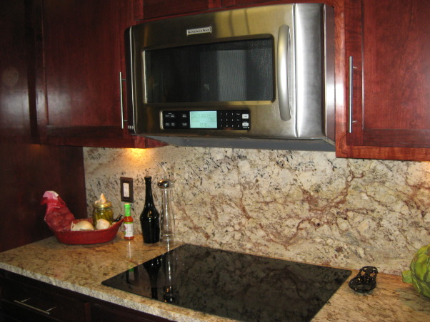 "Kitchen Makeover, Galley kitchen with custom stained cherry cabinets, 18 inch floor tile, stainless steel hardware and appliances including a GE Induction cook top, granite back splash and rough edge granite counter tops for that ""straight from the earth"" look complete with wine fridge. Kohler entree sink is complimented by a Delta Trinsic faucet with Touch2O technology.  The appliances: LG Studio Series Counter depth Refrigerator and Convection Double Oven, KitchenAid Dishwasher and Microwave, Kitchens Design"
