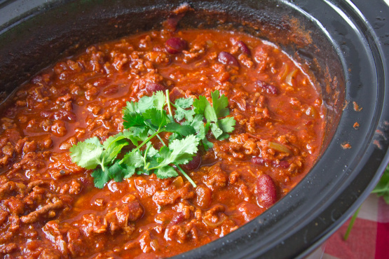 3. Add chili powder and coat the meat and vegetables. Transfer everything into the slow cooker. 4. Add beans, diced tomatoes (including juices), and tomato sauce. Top with water. Stir to mix. 5. Cook on high for 6 hours, or low for 8 hours.