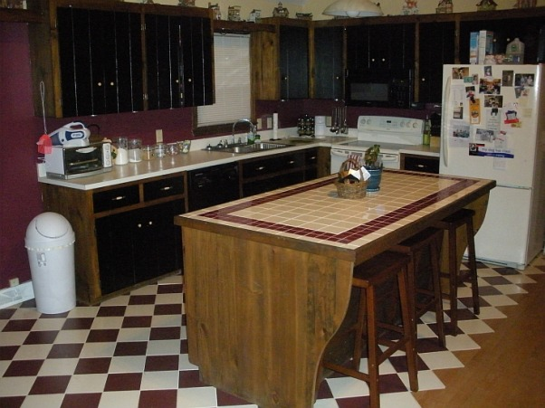 "Who likes maroon?, We recently bought our house with this maroon and black kitchen.  I'm not sure what was being attempted in here but it didn't work.  The cabinets are wood with painted black doors.  The doors aren't all straight but neither are all the cabinet frames.  Maybe it was a theme.  The tile is an off white and maroon transitioning into the hardwood floors of the living room.  The kitchen and living room are one large space with cathedral ceilings.  I think it has a lot of potential.  We have Brazilain Walnut 5"" hardwood picked out for the living room and kitchen.  Any suggestions on color of cabinets/walls.  We're going to gut this thing and start over.  We thought about repainting the cabinets but they're so poorly put together....or time has not been good to them., Maroon, black, poor craftsmanship, oh my!  , Kitchens Design"