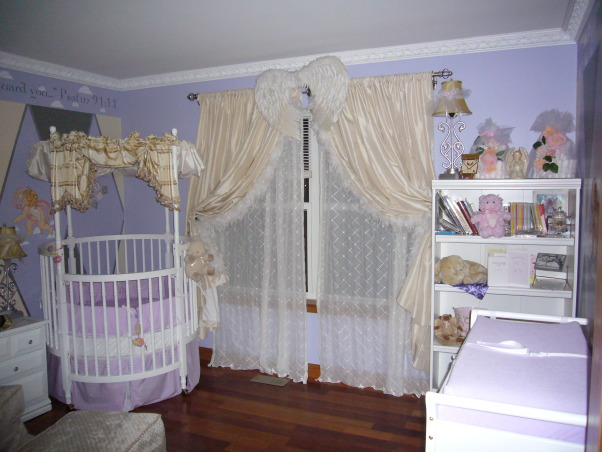 Baby Angel Room, Angel Themed nursery with periwinke, yellow, grey & white colors with silver as accent color.  Two walls have three angels stenciled on the middle of the walls. Round crib in corner of room and full open wings above window and closet., Another view of the angel wings above the window., Nurseries Design