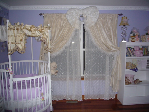 Baby Angel Room, Angel Themed nursery with periwinke, yellow, grey & white colors with silver as accent color.  Two walls have three angels stenciled on the middle of the walls. Round crib in corner of room and full open wings above window and closet., Angel themed room has angel wings above the window with feathers on the inside of the curtains with sheer curtains underneath., Nurseries Design