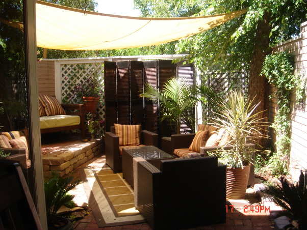 small patio oasis, prior to last summer this space was only brick and mud destroyed by our dog. We attepted to transform it into a retreat for family and friends. the cover is a poly-plastic type cover that is porous and rain can go through. I bought it from target on line. the screen is not anchored but free standing like any indoor screen would be., view from the patio door-space is 16'x20'--tarp I bought on line at Target..several shapes and sizes available. also blue and green.    , Patios & Decks Design