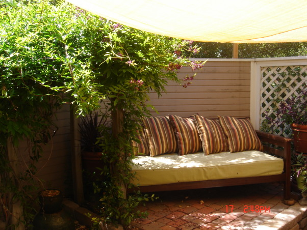 small patio oasis, prior to last summer this space was only brick and mud destroyed by our dog. We attepted to transform it into a retreat for family and friends. the cover is a poly-plastic type cover that is porous and rain can go through. I bought it from target on line. the screen is not anchored but free standing like any indoor screen would be., raised section with bench that covers old tree stump that couldn't be ground. multi-level makes patio seem and look larger.    , Patios & Decks Design