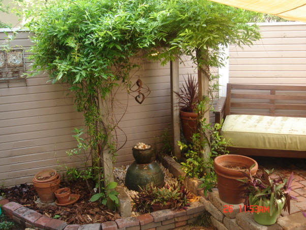 small patio oasis, prior to last summer this space was only brick and mud destroyed by our dog. We attepted to transform it into a retreat for family and friends. the cover is a poly-plastic type cover that is porous and rain can go through. I bought it from target on line. the screen is not anchored but free standing like any indoor screen would be., trellis with carolina jasmine, confederate jasmine and summer wisteria vines and fountain i made-water disappears into the ground.(actually to a large plastic bucket buried beneath the large pots.)    , Patios & Decks Design