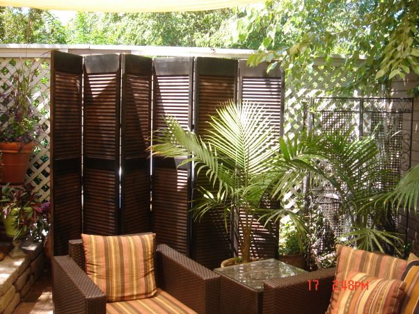small patio oasis, prior to last summer this space was only brick and mud destroyed by our dog. We attepted to transform it into a retreat for family and friends. the cover is a poly-plastic type cover that is porous and rain can go through. I bought it from target on line. the screen is not anchored but free standing like any indoor screen would be., painted louvered closet doors to make screen to hide the grill-free standing-not anchored and yes during one storm they blew over.    , Patios & Decks Design