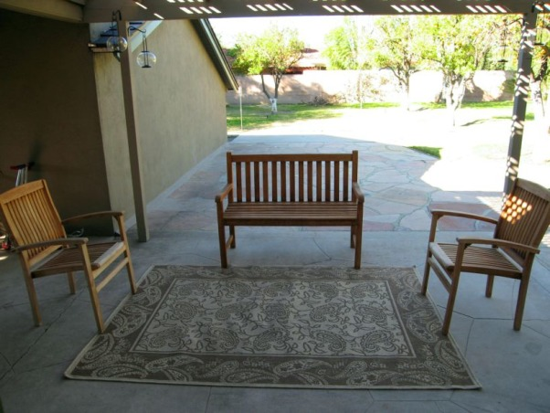 "Wanted: Warm, Romantic Outdoor Patio Living Space, This it our backyard patio that is just outside our living room. It can easily be viewed from the living room through the 12'-wide wall of glass and slider that separates the living room from the patio. Since the patio is right there ""in your face"" (from the living room), we want the patio to look like an extension of the house--like a large, inviting family room that pulls people in encouraging them to sit, relax and enjoy. Instead we have this cold, uninviting patio that we almost never use. It's so unappealing that I hung velvet drapes over the 12'-wide wall of glass in my living room so I wouldn't have to look at it. Please help me create a warm and romantic outdoor living space that my family and friends can enjoy year-round and allow me to remove the current velvet barrier once and for all!, This is the ""family room"" section of our patio. To watch tv, we have to open the siding glass door (that leads to the living room inside the house, and push our heavy out-dated tv (that's in the living room around so it can been seen from outside. Plus the sun sets behind the bench so we're thinking outdoor curtain panels or drapes would protect the space from the sun as well as add appeal.  , Patios & Decks Design"