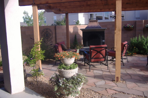 Outdoor Living In Albuquerque, Large paver patio with a fireplace and covered by a natural wood pergolla, flower beds beautiful landscape lighting and a small bistro patio, view of patio from house  , Patios & Decks Design