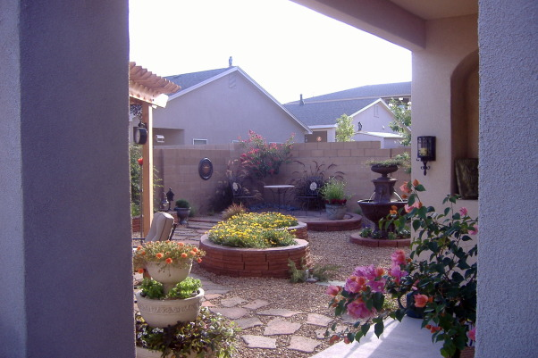 Outdoor Living In Albuquerque, Large paver patio with a fireplace and covered by a natural wood pergolla, flower beds beautiful landscape lighting and a small bistro patio, Flower bed and bistro patio  , Patios & Decks Design