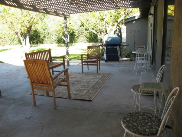 "Wanted: Warm, Romantic Outdoor Patio Living Space, This it our backyard patio that is just outside our living room. It can easily be viewed from the living room through the 12'-wide wall of glass and slider that separates the living room from the patio. Since the patio is right there ""in your face"" (from the living room), we want the patio to look like an extension of the house--like a large, inviting family room that pulls people in encouraging them to sit, relax and enjoy. Instead we have this cold, uninviting patio that we almost never use. It's so unappealing that I hung velvet drapes over the 12'-wide wall of glass in my living room so I wouldn't have to look at it. Please help me create a warm and romantic outdoor living space that my family and friends can enjoy year-round and allow me to remove the current velvet barrier once and for all!, The patio is lattice-covered (not fully covered so we're afraid to put nice furniture for fear of it getting ruined. We're thinking a fully-covered patio is the way to go--plus we'll be able to use the patio even if it's raining. Lighting is also needed because our patio tends to be dark. Any lighting suggestions? Also, the old cement is cracked and uneven. What should we replace it with?  , Patios & Decks Design"