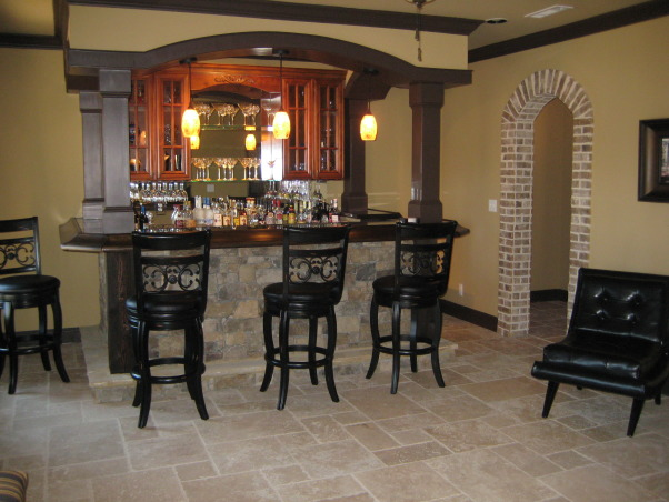 Tuscan Basement , My husband & I completely designed our basement. We told and drew pictures for our contractor on what we wanted. Our basement was nothing but 2x4's and windows since we had the house built. We wanted it to have an old world Tuscan feel with a little more luxury. We live on a lake in subdivision and it's about time we took advantage of the space and windows that overlook the lake. All the stacked stone is real, natural travertine, and real brick from Boral. It was a 3mo. labor of love coordinating,researching, and picking everything out. We still have some more decorating to do(theater room,workout area) but all in all we are very pleased how it has turned out. Every item we purchased was either clearance or on sale. We got a deal on everything we purchased for the basement. , Bar area to the right of the stairs        , Basements Design