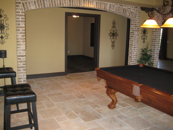 Tuscan Basement , My husband & I completely designed our basement. We told and drew pictures for our contractor on what we wanted. Our basement was nothing but 2x4's and windows since we had the house built. We wanted it to have an old world Tuscan feel with a little more luxury. We live on a lake in subdivision and it's about time we took advantage of the space and windows that overlook the lake. All the stacked stone is real, natural travertine, and real brick from Boral. It was a 3mo. labor of love coordinating,researching, and picking everything out. We still have some more decorating to do(theater room,workout area) but all in all we are very pleased how it has turned out. Every item we purchased was either clearance or on sale. We got a deal on everything we purchased for the basement. , Pool room looking towards theater room.         , Basements Design
