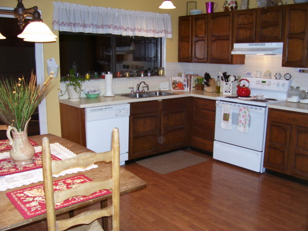 """Our hodge-podge kitchen, I love the space in our kitchen and the fact that it is an eat-in.  However, I would love to have some suggestions on what to do with our cabinets, counters, and layout.  Our countertops are laminate and they are """"bubbling"""" up in several spaces.  I love the space of our cabinets but am not fond of the color/doors.  We bought our home after it had been mistreated for years.  We've updated every room but the kitchen and bathroom.  I would describe our style as simple, classic, traditional.  We are not into modern and sleek.  , I wish that our colors were more uniform/coordinated.    , Kitchens Design"""