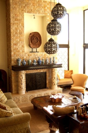 Bali Living Room, I fell in love with Bali and all its beauty, so I designed this beach house with Indonesian elements. From stone and wood carvings to daybeds and sheer canopies, Bali influence is everywhere you look. Since this is a vacation home, and sticking to the budget was essential, we decided to import a container of teak furniture, marble tile, sinks, doors and art from Bali. The chandelier is a Moroccan design it's made from metal with white fabric inside. The Chinese vases I collected over the years. We used picture frame  molding to create the fireplace mantel. I like mixing furniture so in this living room I used an antique wing chair, a carved wooden bench, and a large plush sofa from Z GALLERY., This fireplace is16' tall by 8' wide.We used tumbled marble in cream and saffron on the fire place facade. I kept all the colors neutral and organic. Because this is a casual beach house, I did not want to take away from the natural beauty of the ocean.              , Living Rooms Design