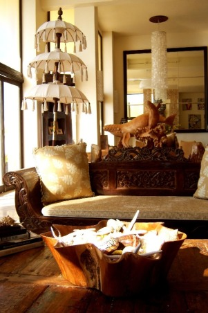 Bali Living Room, I fell in love with Bali and all its beauty, so I designed this beach house with Indonesian elements. From stone and wood carvings to daybeds and sheer canopies, Bali influence is everywhere you look. Since this is a vacation home, and sticking to the budget was essential, we decided to import a container of teak furniture, marble tile, sinks, doors and art from Bali. The chandelier is a Moroccan design it's made from metal with white fabric inside. The Chinese vases I collected over the years. We used picture frame  molding to create the fireplace mantel. I like mixing furniture so in this living room I used an antique wing chair, a carved wooden bench, and a large plush sofa from Z GALLERY., The furnishing in this living room is a collage of antiques and carved teak pieces from Bali.Behind the sofa, you can see a family of sperm whale carving.               , Living Rooms Design