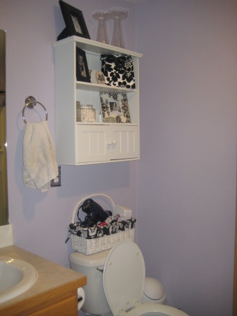 "purple and black and white, It is the master bath and as apprehensive as my husband was about a purple bathroom he thinks that it turned out ""okay."" I actually really love this bathroom and mostly got everything at yard sales, made the curtains myself, and my brother drew the large picture over the tub., I looked forever to find a basket that would fit on top of the toilet to hold my curling iron, hair dryer, and straightener...  , Bathrooms Design"