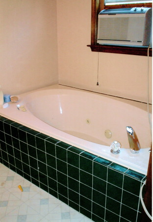 From hideous to spa-tacular!, This was my master bath in one of the houses I flipped.  Before the walls were peach with dark wood trim and hunter green tile with linoleum floor.  Everything was redone from the chandeliers to the marble floor for under 1,000., Tub before.  Not very spa like!  Can you believe the location of the airconditioner?  Hello electrocution!  :)     , Bathrooms