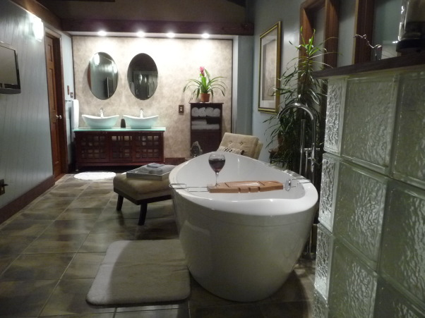 DIY Asian Inspired Spa Bathroom, We converted our 70's bathroom to an Asian inspired, comfortable place to relax.  Features a slipper soaking tub, a steam shower and a flat screen to watch HGTV.  No contractors, designers, or other professionals were used in the making of this remodel!    We have had so many comments about our tub, I wanted to share the link where we purchased it: http://www.bathtubsfactorydirect.com  Vanity was purchased from Costco, as was the additional storage unit.  Paint is Autumn Fog Valspar from Lowes. , Double vanity with glass top and vessel sinks.  Mirrors are medicine cabinets for extra storage.  Additional storage is in the closet to the left of the vanity (part of the walk-in master bedroom closet).         , Bathrooms