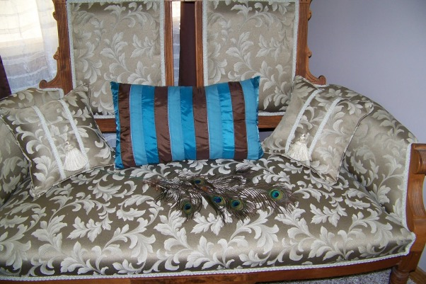 Peacock inspired master bedroom, My bedroom has mocha colored walls and bedding, mocha/almond carpet and a splash of peacock blue in the curtains and accessories. The adjoining master bath has peacock blue walls and coordinates with the bedroom colors., close-up of the loveseat with pillows and peacock feathers.  , Bedrooms Design