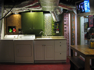 Small Basement Kitchen, This is a basement laundry room area that is also a kitchen. A new kitchen sink was recently installed and I then put up wall board, tiles, wine rack and storage areas. I gave the wall a colorful paint treatment and made unique graphic pantry doors. They are on the right side of the photo. The multi green tiles tie all the colors together., This is after putting up walls, tiles and pantry doors. I painted the walls and cabinet with deep saturated colors  and made pantry doors with graphic designs in complimenting colors.  , Basements Design
