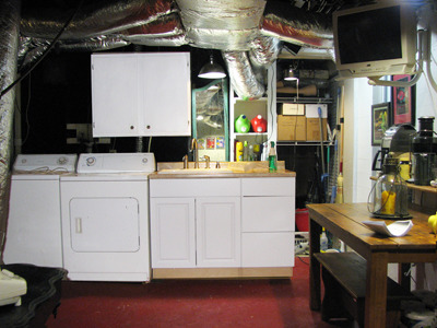Small Basement Kitchen, This is a basement laundry room area that is also a kitchen. A new kitchen sink was recently installed and I then put up wall board, tiles, wine rack and storage areas. I gave the wall a colorful paint treatment and made unique graphic pantry doors. They are on the right side of the photo. The multi green tiles tie all the colors together., This is how it looked before the walls and pantry doors were put up. , Basements Design