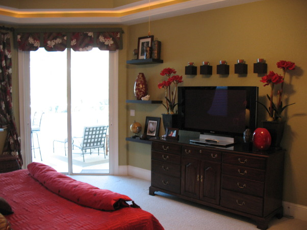 "Stylish Master Bedroom with Eclectic Flair!, My client-friend wanted a bedroom that was romantic, stylish, ""pulled-together"", and had a ""far away"" feel. I worked like crazy for 4 days while she and her husband were away on vacation.  I took my color inspiration from the hawaiian barkcloth fabric I purchased from Hawaii for the window treatments... Most of the larger furniture (although I removed 3-4 pieces) and bedding needed to stay - so I used color, some smaller pieces of furniture, accessories and art to create the space and feeling she wanted. A flokati rug anchored the seating area by the pool window. I built a wood frame and created a valance for the sliders. I did alot of editing of existing ""stuff"" in the room and pared it down with all new art and accessories. I painted an accent wall in ""bordeux"" and glazed the architectural detail to create visual impact. I changed the pillows on the bed which gave the focal point some pizazz! I created a headboard with an iron art piece and carved wooden art plaques.  I bought new lighting for each end table as well as romantic lighting for sitting area and chest.  I was relieved after the ""reveal"" as she and her husband were estatic!, AFTER - View of the valance , Bedrooms Design"
