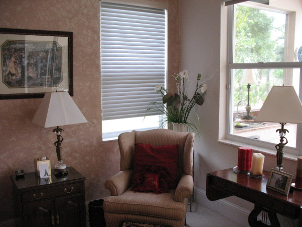 "Stylish Master Bedroom with Eclectic Flair!, My client-friend wanted a bedroom that was romantic, stylish, ""pulled-together"", and had a ""far away"" feel. I worked like crazy for 4 days while she and her husband were away on vacation.  I took my color inspiration from the hawaiian barkcloth fabric I purchased from Hawaii for the window treatments... Most of the larger furniture (although I removed 3-4 pieces) and bedding needed to stay - so I used color, some smaller pieces of furniture, accessories and art to create the space and feeling she wanted. A flokati rug anchored the seating area by the pool window. I built a wood frame and created a valance for the sliders. I did alot of editing of existing ""stuff"" in the room and pared it down with all new art and accessories. I painted an accent wall in ""bordeux"" and glazed the architectural detail to create visual impact. I changed the pillows on the bed which gave the focal point some pizazz! I created a headboard with an iron art piece and carved wooden art plaques.  I bought new lighting for each end table as well as romantic lighting for sitting area and chest.  I was relieved after the ""reveal"" as she and her husband were estatic!, Bedrooms Design"