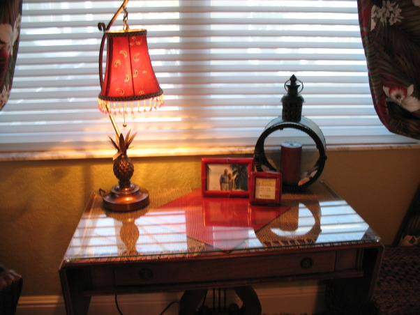 "Stylish Master Bedroom with Eclectic Flair!, My client-friend wanted a bedroom that was romantic, stylish, ""pulled-together"", and had a ""far away"" feel. I worked like crazy for 4 days while she and her husband were away on vacation.  I took my color inspiration from the hawaiian barkcloth fabric I purchased from Hawaii for the window treatments... Most of the larger furniture (although I removed 3-4 pieces) and bedding needed to stay - so I used color, some smaller pieces of furniture, accessories and art to create the space and feeling she wanted. A flokati rug anchored the seating area by the pool window. I built a wood frame and created a valance for the sliders. I did alot of editing of existing ""stuff"" in the room and pared it down with all new art and accessories. I painted an accent wall in ""bordeux"" and glazed the architectural detail to create visual impact. I changed the pillows on the bed which gave the focal point some pizazz! I created a headboard with an iron art piece and carved wooden art plaques.  I bought new lighting for each end table as well as romantic lighting for sitting area and chest.  I was relieved after the ""reveal"" as she and her husband were estatic!, AFTER - Antique table looking like new!, Bedrooms Design"
