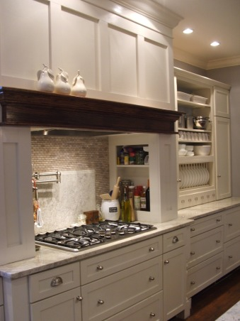 The look for a lot less-before & after, transitional kitchen style.  i spent a lot of time pricing and revising plan to achieve a custom kitchen look without the price tag.  because i love to cook but hate to clean, function was just as important as aesthetics.  behind pocket door (left of ovens) is my pantry with custom looking cabinets and wood countertops (home depot unfinished cabinets w/ trim molding added and salvaged wood countertops) w/ built-in microwave and prep sink. (photos to come- need to paint cabs), To save money but still have great cooking, i designed this cooktop unit.  Gas cooktops are alot cheaper than a stove unit and also look very clean. (functions great to!   Because hood unit cabinetry was way to expensive thru cab. manuf. i created my own with plywood and matched cabinet paint and the mantel stained same as island.  Open spice racks on both sides and pot filler makes this cook area fun and easy to use.  the large drawer cabinets makes storage of pots and pans simple.  my kitchen is not large but everything has its place.  went cheap with gas cook top allowed me to purchase double oven unit and warming drawer, which we installed in a drywall wall and painted with same glossy white as cabinets. a look that is incredibly cheaper than oven cabinets. and with wall ovens built-in, i avoided the awkward depth and unwanted focus that oven cabinets can produce.               , Kitchens Design