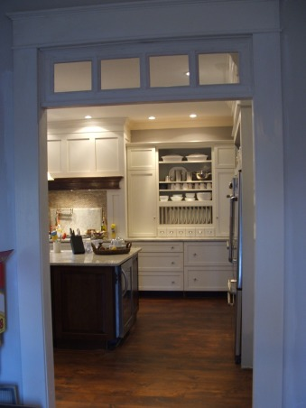 "The look for a lot less-before & after, transitional kitchen style.  i spent a lot of time pricing and revising plan to achieve a custom kitchen look without the price tag.  because i love to cook but hate to clean, function was just as important as aesthetics.  behind pocket door (left of ovens) is my pantry with custom looking cabinets and wood countertops (home depot unfinished cabinets w/ trim molding added and salvaged wood countertops) w/ built-in microwave and prep sink. (photos to come- need to paint cabs), This is the view from dining room, currently being painted. I also still need to add furniture feet trim on base cabinets.  When we remodeled first floor, we removed all 80's trim around doorways, widen all opens to a uniform 4'. and my husband with help built transoms. trim is nothing more than pine 1x6 boards. transoms' glass was reused from aluminum windows we replaced. On the island is an undercounter beverage refrigerator, highly recommend. we purchased all jenn-air appliances which provided us with a big discount and i think the expensive look of higher priced equipment without the enormous price tag. Because this room was orginally our living room, the naste 80's carpet had to go.  I love Carlisle Wide Plank Flooring,  their reclaimed hard woods were out of our price point, but Deb at Carlisle gave me a great deal on eastern white pine. I love our random width (6"" to 12"" wide t&g boards.  The pine is easy on the feet and creates the beautiful character as it wears. Personal Note: We did make the mistake, because of our timeline, of hiring a local stainer- or so he said he was- to stain and tung oil our new floors without seeing previous projects. needless to say i am still fixing his work- if it can be called that. You know who you are, at least take a course on staining before you contract out your lack of skills!               , Kitchens Design"