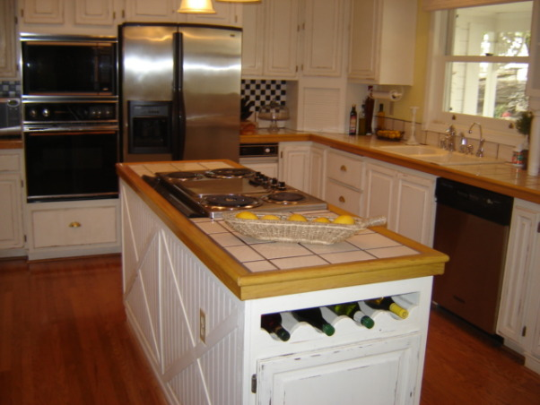 French country, Kitchen in pale yellow with white cabinets.Hardwood floors., Built in wine bottles, Kitchens Design