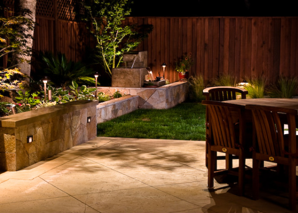 Outdoor Kitchen and Eating Area, Our backyard is small (21x52) and we made the most out of the space we have.   We love to sit outside with a glass of wine and enjoy the evening., Patio area and yard showing rock wall and fountain and outdoor lighting.  Outdoor lighting is the key - I think it is the most important because it creats atmosphere or kills it is not done right.               , Outdoor Spaces