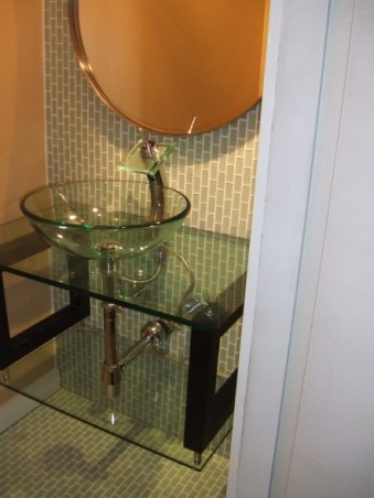 Sleek, modern, small bathroom, I updated a small and very outdated half bathroom.  I installed glass tile, glass vanity, glass sink, and glass faucet to create very airy feel.  I ran the tiles (subway pattern) verticaly to elongate the room.  I used the same tile on floor and wall to create illusion of length., Small hallway half-bath: All glass (tile, vanity, sink, faucet).  Subway tiles laid vertically to elongate the length of the small powder room.  Same tile on floor and wall to create an illusion of length.       , Bathrooms Design