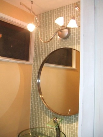 Sleek, modern, small bathroom, I updated a small and very outdated half bathroom.  I installed glass tile, glass vanity, glass sink, and glass faucet to create very airy feel.  I ran the tiles (subway pattern) verticaly to elongate the room.  I used the same tile on floor and wall to create illusion of length., Round mirror and bent track to break up the very square room and tiles.     , Bathrooms Design