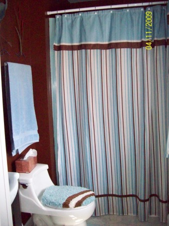 Hubby's small bathroom, Small 3/4 bath..Went from light blue to chocolate brown, Changed the toilet to white.  Added blue and brown shower curtain ,towels and bath mat set. Across from the vanity is a window that I made a curtain from another shower curtain. , Bathrooms Design