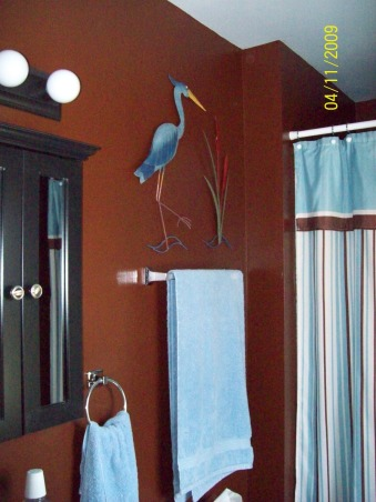 Hubby's small bathroom, Small 3/4 bath..Went from light blue to chocolate brown, New color walls chocolate brown. Blue Heron and cattails are metal. I thought the dark color might make the room look smaller. But with the smaller vanity it made it seem bigger.  , Bathrooms Design