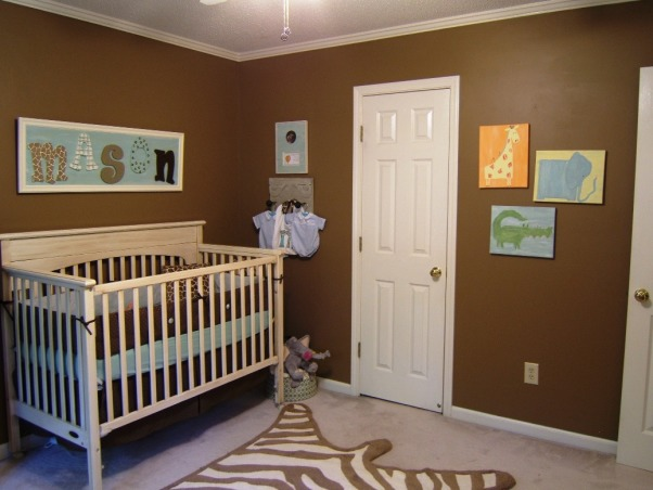 "Baby Boy's Jungle Room, This boy's nursery was also done on a budget. I chose my fabrics first and decided to go with chocolate brown and a robin's egg blue (which morphed into more of an aqua). Initially I wasn't sure of a ""theme"" but knew that I wanted a rustic feel. The zebra rug, sock monkey, and giraffe display made it obvious that subconciously I had chosen a jungle theme =)  Here is the furniture cost breakdown: Convertible Dropside Crib @ Target.com.....$125 Changing Dresser @ JC Penney.....$170 Bookshelves @ JC Penney.....$100 Dutailier Glider & Ottoman (a splurge!) @ Albee Baby.....$570 Rug @ Target.com.....$53  With much planning and a tremendous amount of help from Gigi (my mom), this room has come to be one of my favorites. Hope you enjoy!,  This is the closet door view of the room. There's an old piece of molding with doorknobs that serves as a hanging plaque for a couple of Feltmann Brothers outfits (including Mason's ""take home"" romper) and a birth announcement is framed above the plaque.   , Nurseries Design"