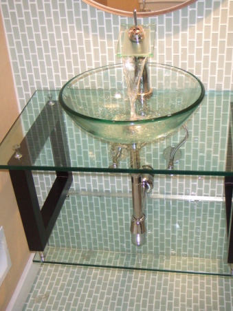 Sleek, modern, small bathroom, I updated a small and very outdated half bathroom.  I installed glass tile, glass vanity, glass sink, and glass faucet to create very airy feel.  I ran the tiles (subway pattern) verticaly to elongate the room.  I used the same tile on floor and wall to create illusion of length., I love this faucet!  Glass vanity, glass vessel sink, glass faucet. , Bathrooms Design