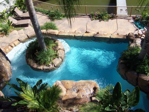 Exotic Pool Pics, Our pool was built on a small slopping lakefront yard. We have a slide, 2 waterfalls, spa, vanishing edge, palm tree in pool, and a 35 x 10 foot rook cave which enters into a movie room, bath and workout room. My wife and I did all the planting and gave it a beautiful tropical look. This is our daily exotic gettaway. , pool with palm tree island, Pools Design