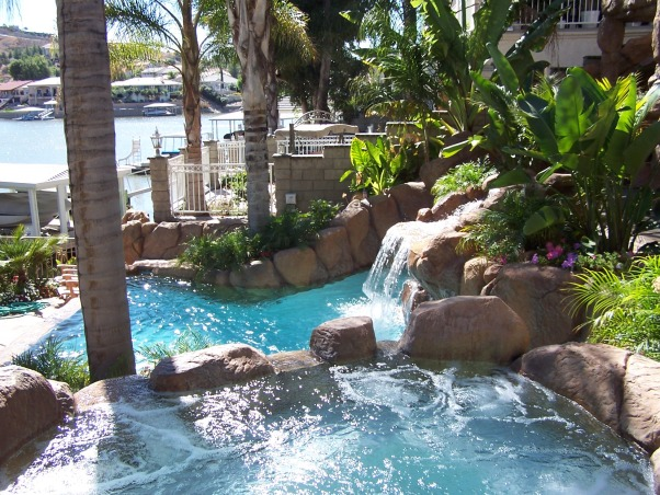 Exotic Pool Pics, Our pool was built on a small slopping lakefront yard. We have a slide, 2 waterfalls, spa, vanishing edge, palm tree in pool, and a 35 x 10 foot rook cave which enters into a movie room, bath and workout room. My wife and I did all the planting and gave it a beautiful tropical look. This is our daily exotic gettaway. , Pool, spa, waterfall, lake view., Pools Design