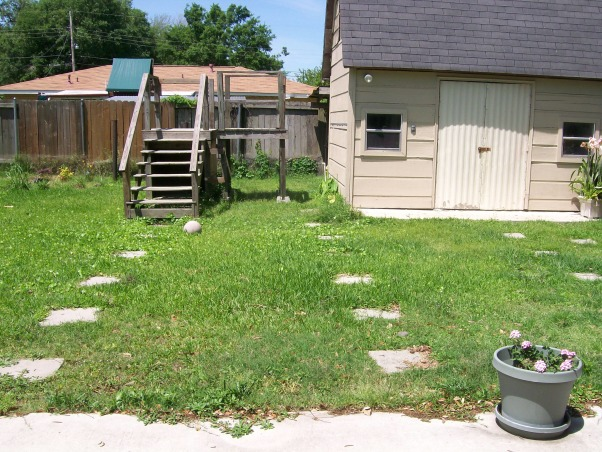 "Backyard Catastrophe, Stairs to nowhere, 40 randomly placed stepping stones, uneven ground...What were they thinking? This is our first house and we really want to clean up the backyard.  It is truly a safety hazard! As I was out taking pictures, I stepped down off of the steps to nowhere and broke my foot on the stepping stone at the bottom! Yesterday, my father-in-law picked up most of the stepping stones and removed the stairs. But we still have a long way to go! We want to arrange the 16 inch stepping stones in a patio format and get some nice patio seating. The shed is somewhat in the way though. We plan to remove the dog fence and tetherball pole. Of course our plants are random and overgrown; we want to rearrange and remove some of them. We need ideas! HELP!, The ""Stairs to Nowhere""- we think this used to be an access to the top of the shed. But now...its just an eyesore! (my father-in-law tore it down the day after I broke my foot on it- so now it is a barren spot of yard), Yards Design"