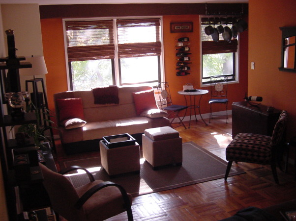 "Studio Apartment - Living Room / Bedroom combo, A studio apartment in NYC - a few miles outside of Manhattan.  Only about 500 square feet, there is still plenty of living and storage space!  Bamboo shades to allow lots of light; storage ottomans that double as coffee tables; a couch that easily folds down into a bed, but also has a large storage area underneath;  and, of course, the 42"" plasma TV on the wall :-), Living area w/ storage ottomans, futon, and a folding console table that can seat the whole family! , Living Rooms Design"