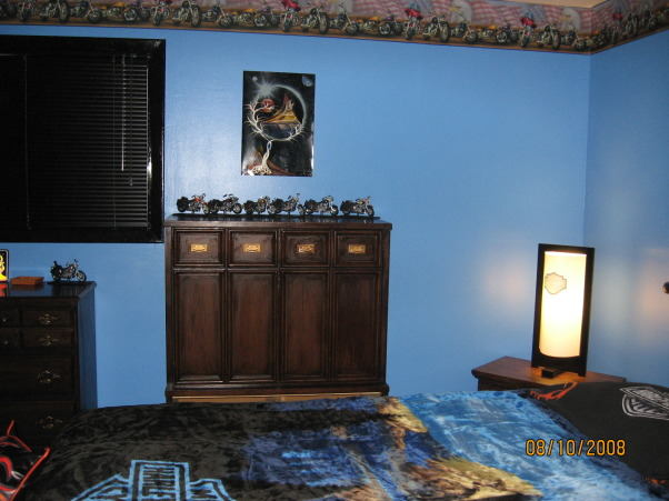 Harley Davidson Room, Started out totally white with dirty mauve carpet., Painted walls blue, all woodwork black, hung Harley Davidson border, and collection of Harleys displayed on chest of drawers. , Bedrooms Design