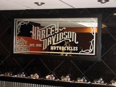 Harley Man Cave, This is my husband's ode to Harley Davidson/Crown Royal Man Cave., I designed the custom Harley Davidson mirror based on a wooden sign at one of the dealerships we visited. It is mounted to our black galaxy granite wall, that has an oak chair rail., Basements Design